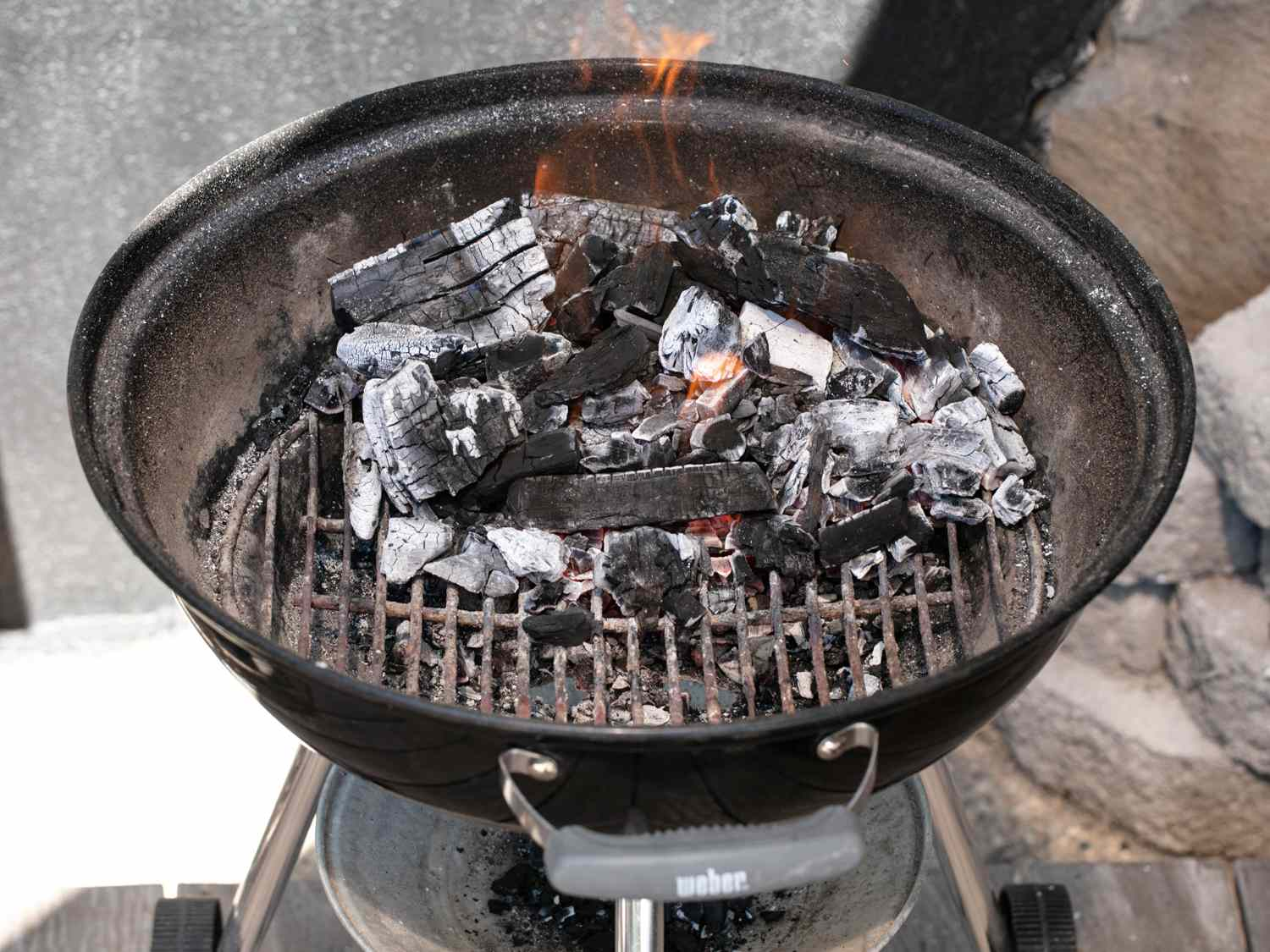 Hot hardwood charcoal on one side of a kettle grill.