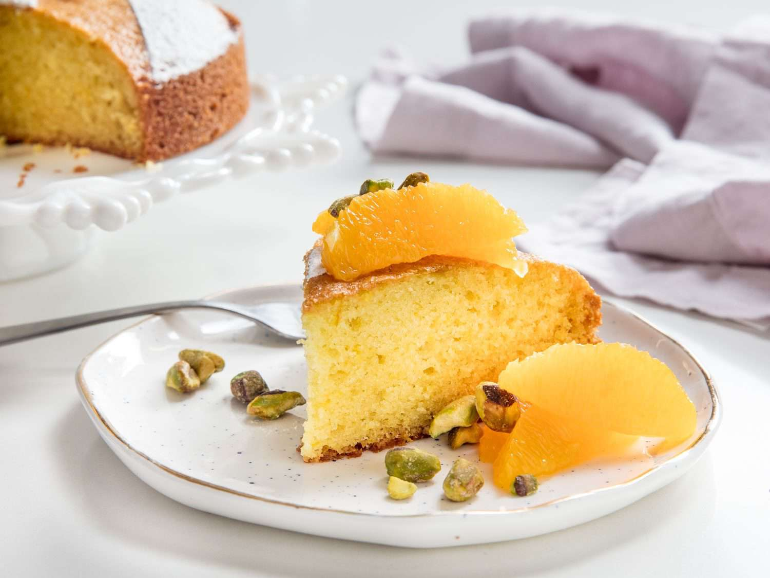a slice of olive oil cake with fresh fruit and pistachios