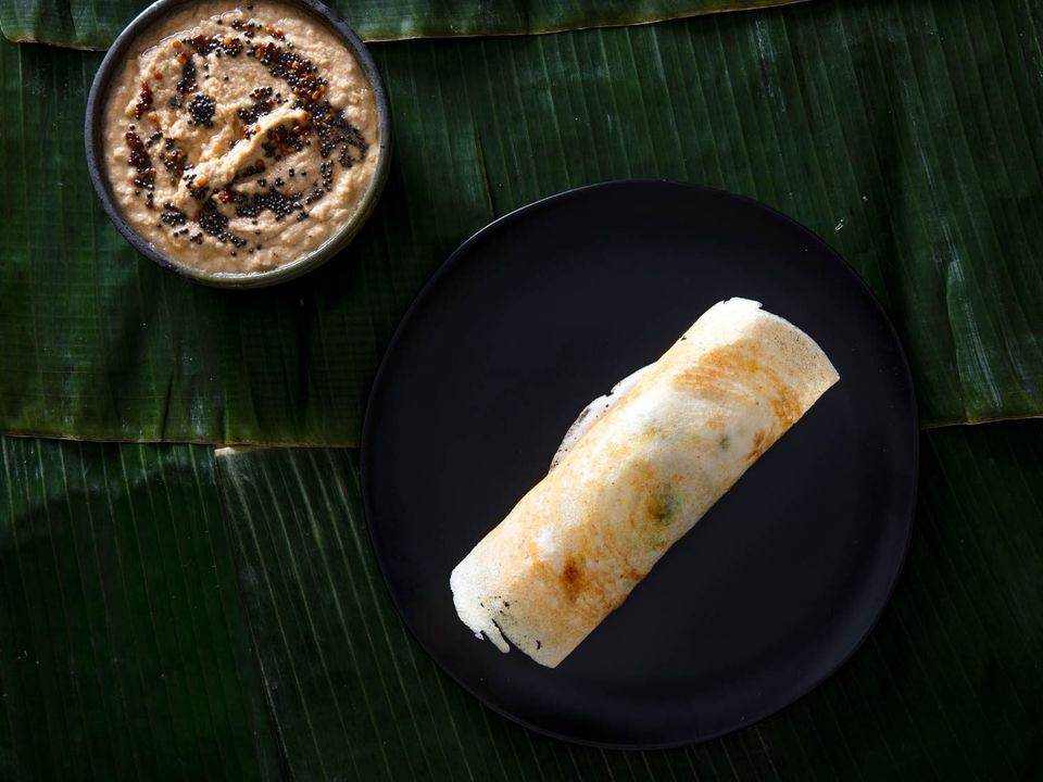A dosa on a plate with a side of coconut chutney