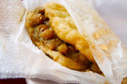 A doubles sandwich filled with curried chickpeas.