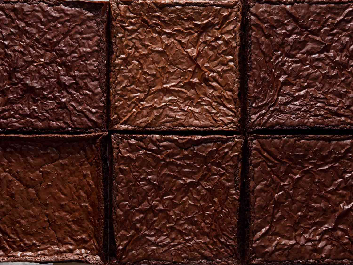 Overhead close-up of the crackly, dark-brown surface of brownies