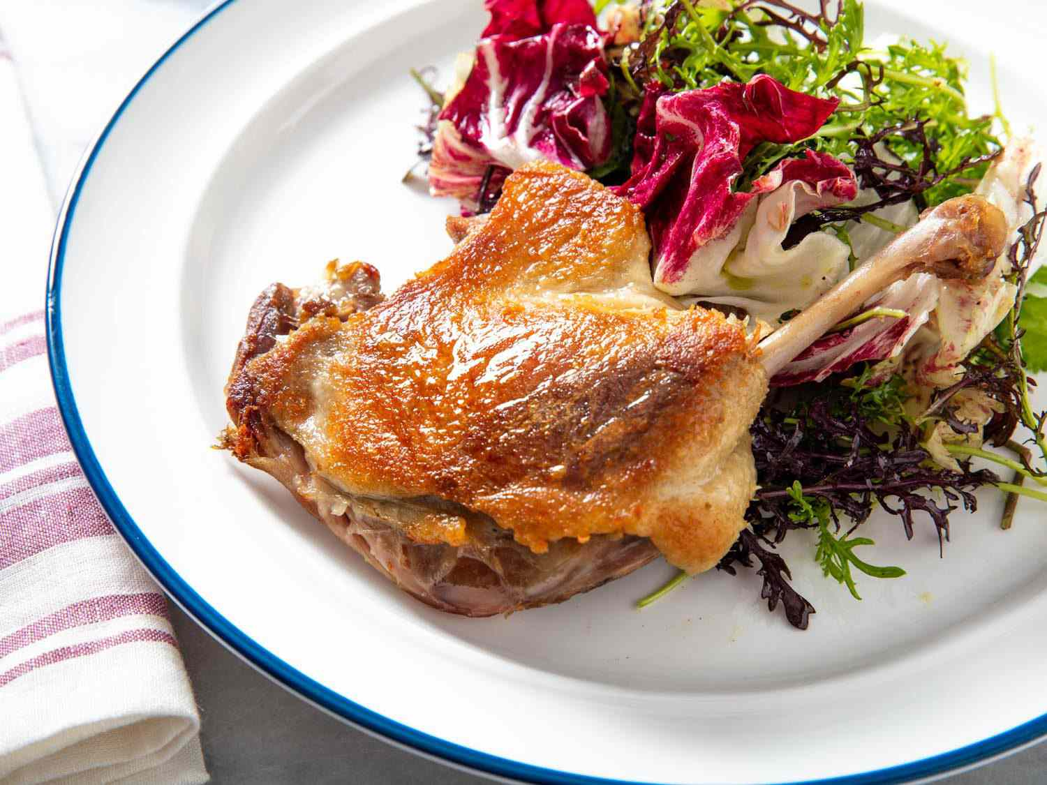 Closeup side view of a crisped confit duck leg with a mixed greens salad.