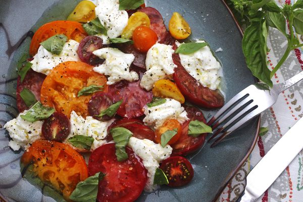 A caprese salad with heirloom tomatoes, mozzarella, and fresh basil on a plate with a fork and knife.