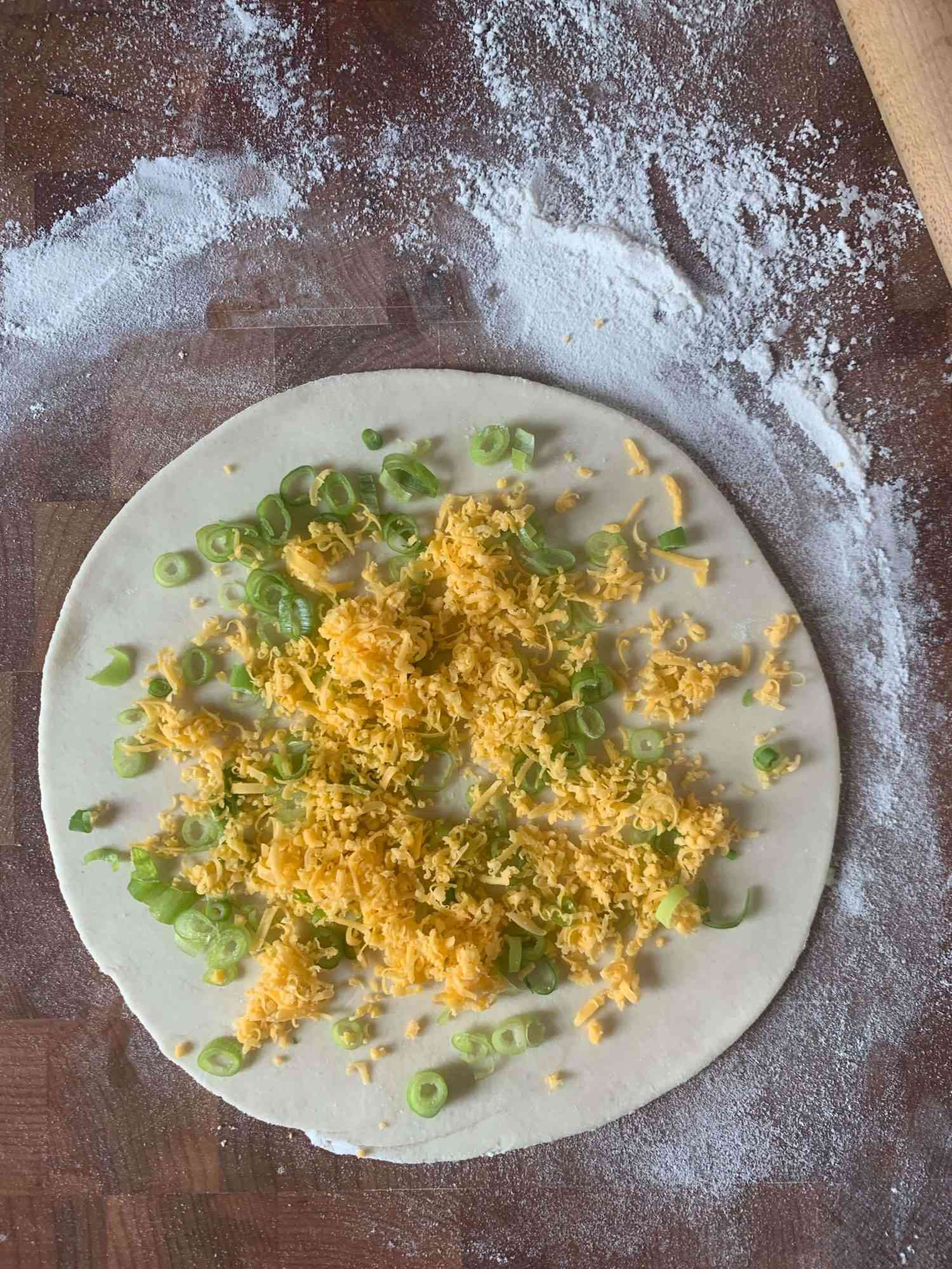 scallion pancake dough with scallions and cheese sprinkled over it