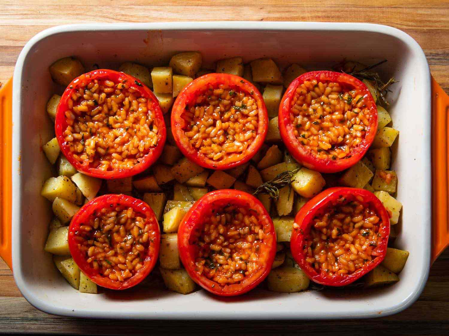 Overhead of rice-stuffed tomatoes in a baking dish with potatoes before being roasted.