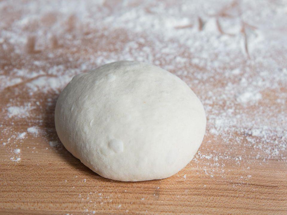 a ball of pizza dough on a floured work surface
