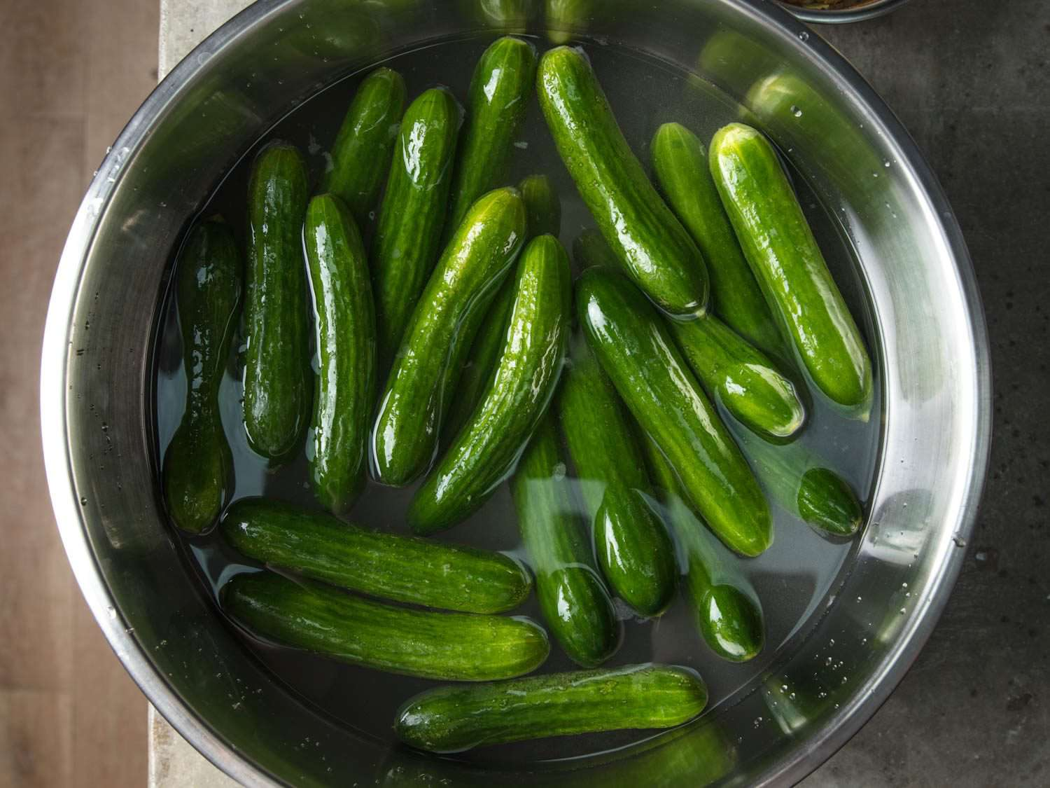Overhead view of bowl with small cucumbers soaking in salt water as a preparatory step before pickling