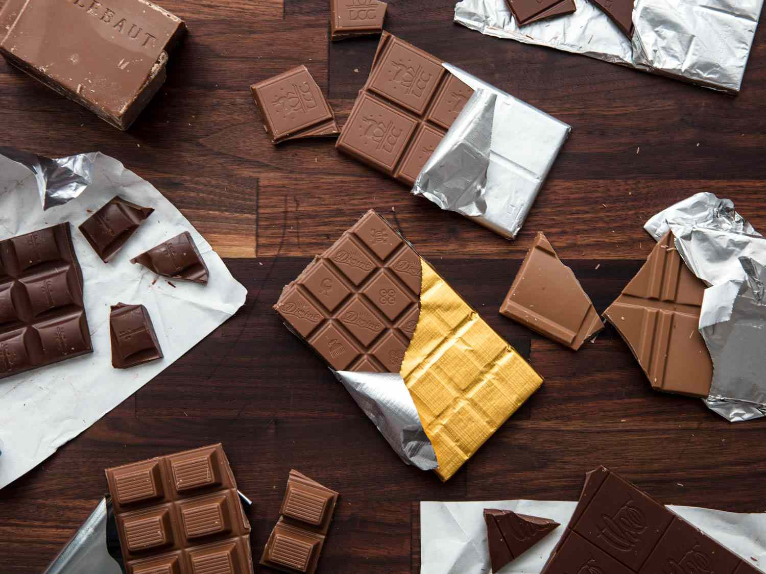 An assortment of milk chocolate bars, unwrapped or partially wrapped, arranged on a wooden background