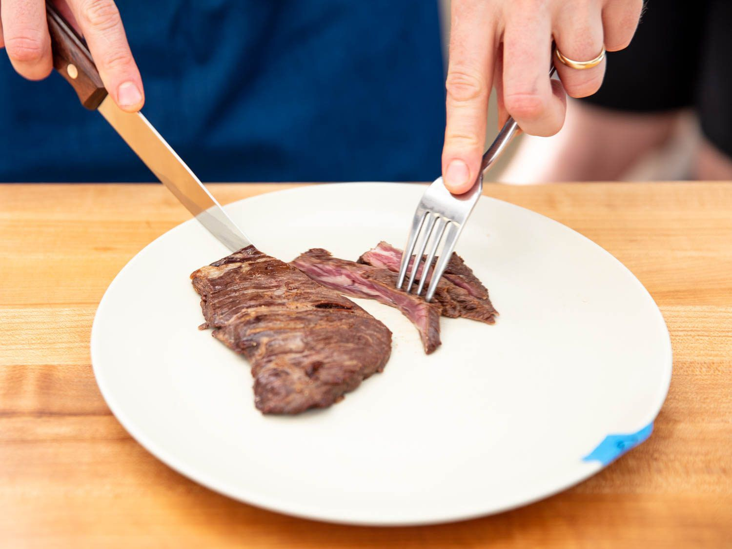 Slicing into a rare hanger steak with a steak knife.
