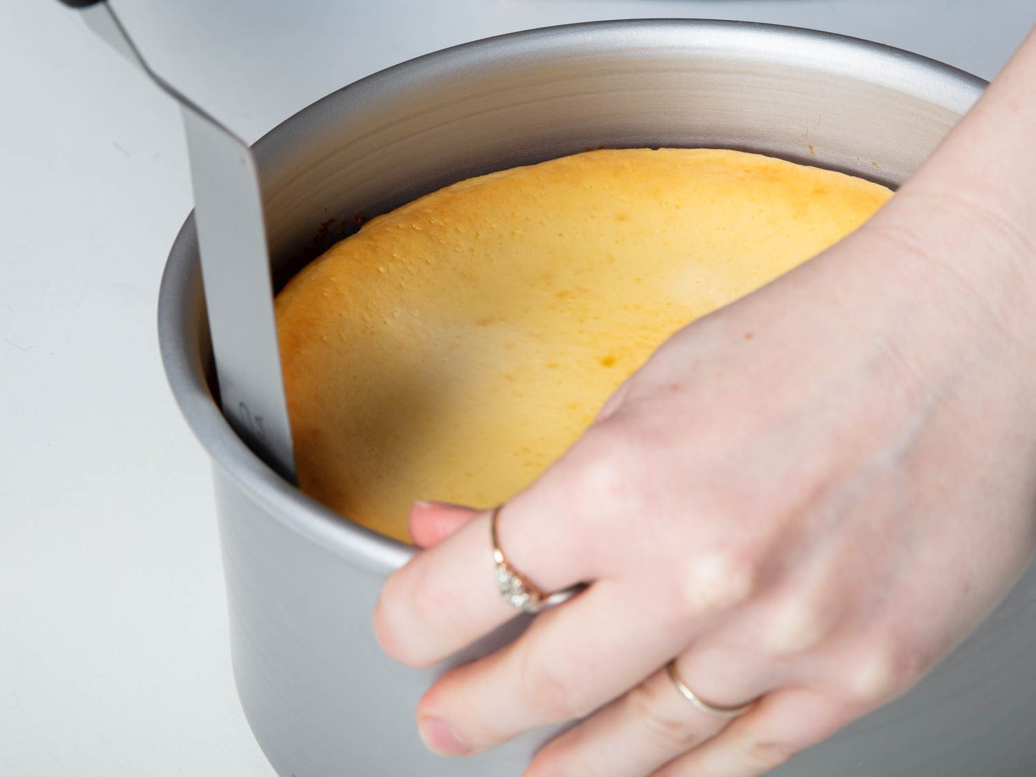 The baked cheesecake being loosened from the pan with a large offset spatula, which is being run along the interior edge of the pan