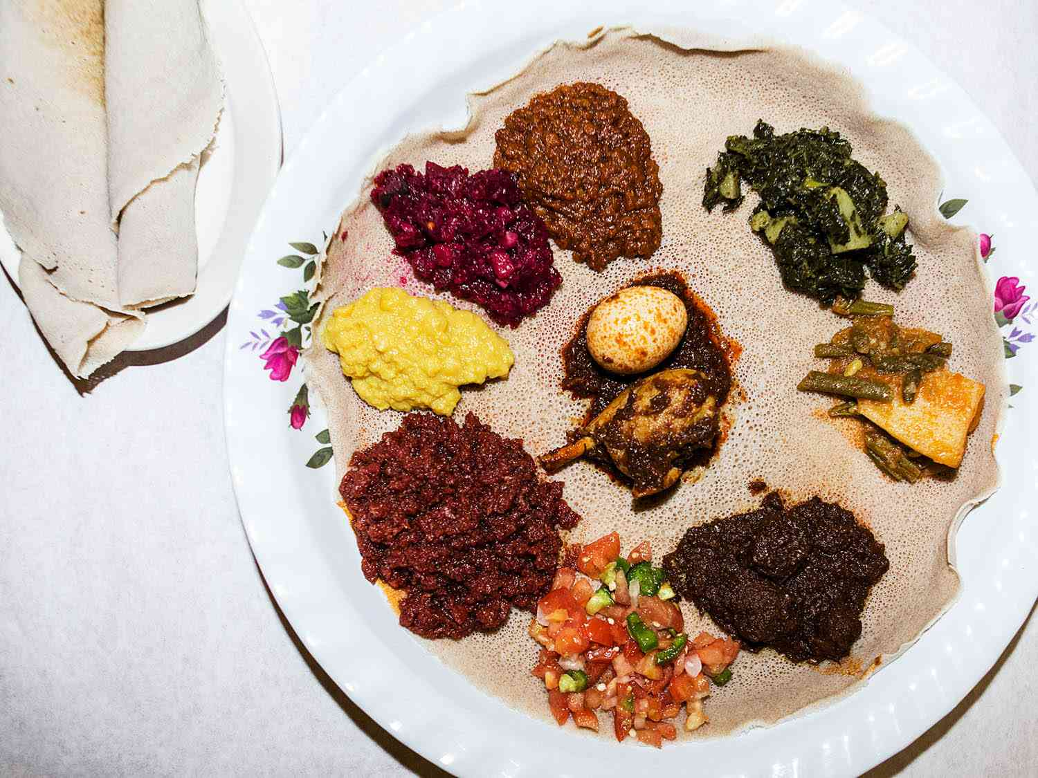 Ethiopian injera bread holding servings of vegetable dishes.