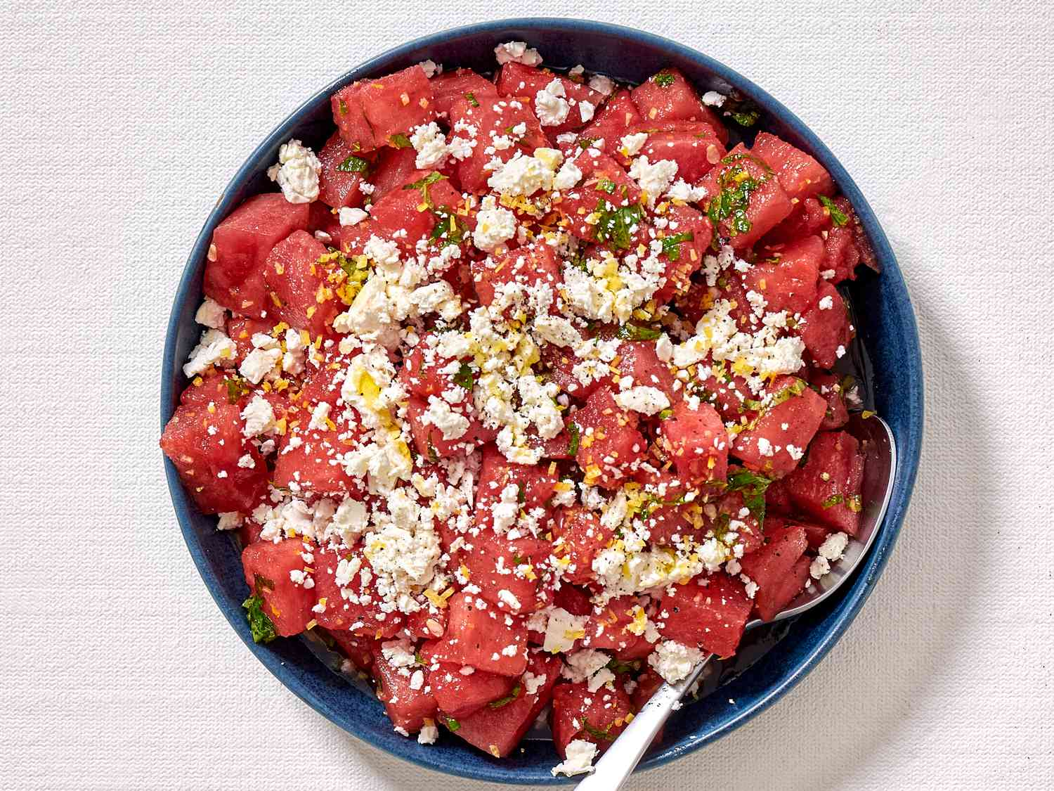 A watermelon salad with feta cheese, mint, and lemon zest in a large blue bowl.