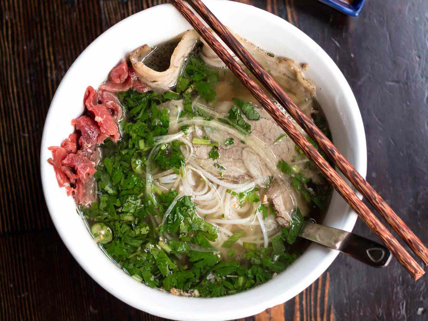 Overhead shot of bowl of pho with meat, noodles, herbs, and a pair of chopsticks resting on the side of the bowl