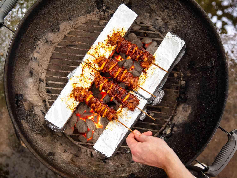 Overhead shot of al pastor skewers grilled using the skewer set-up for a kettle grill