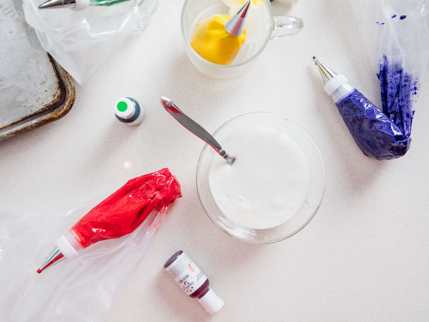 Tools for frosting cookies with colorful royal icing: bowl of plain white royal icing, bottles of gel paste food dye, and piping bags of colored icing in red, yellow, and blue
