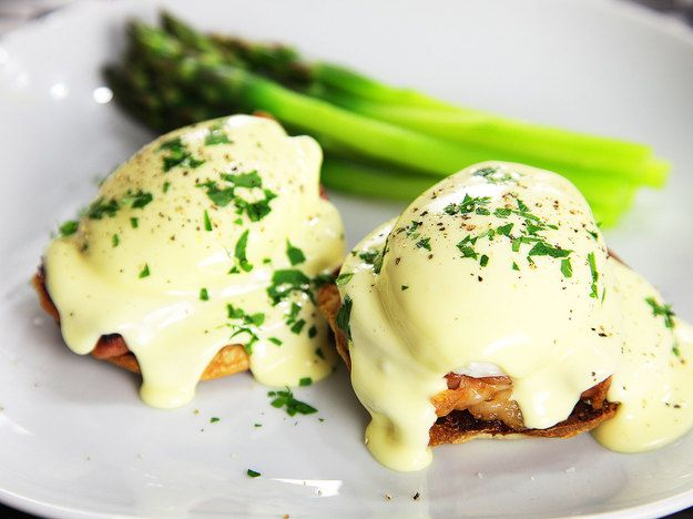 A plate with two foolproof eggs Benedict and asparagus spears.