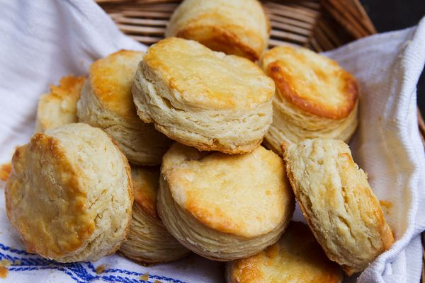 A towel-lined basket full of buttermilk biscuits.