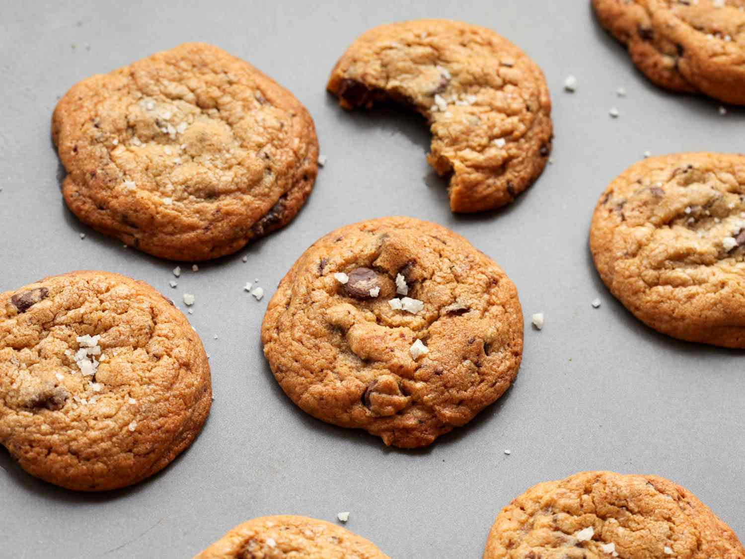 Chocolate chip cookies on a grey background with one cookie with a bite taken out.