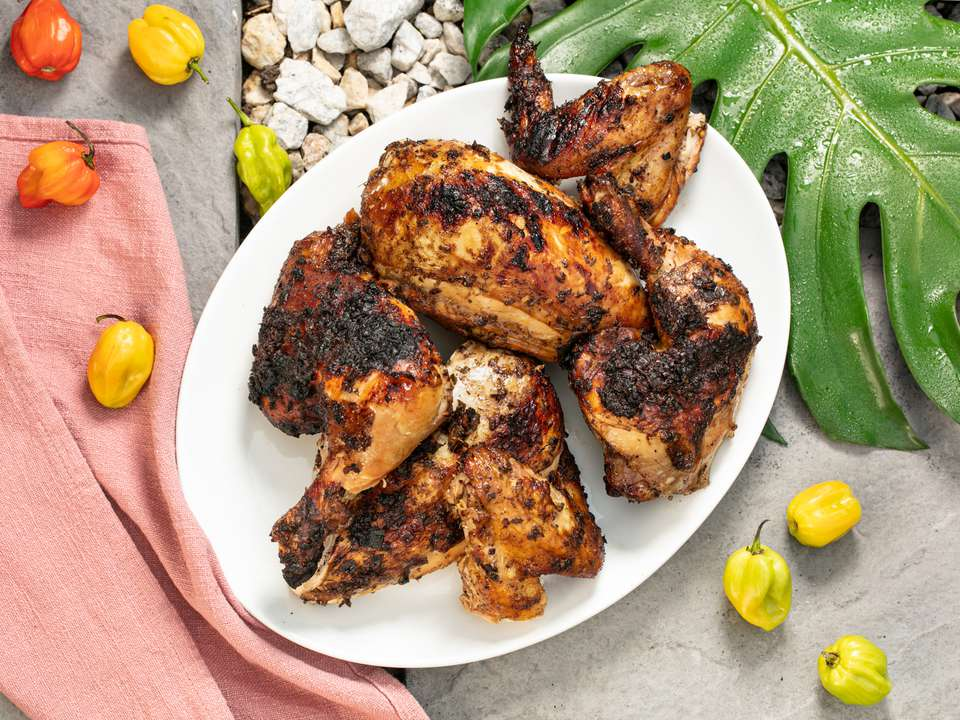 Spicy grilled jerk chicken on a white platter with scotch bonnet peppers surrounding it