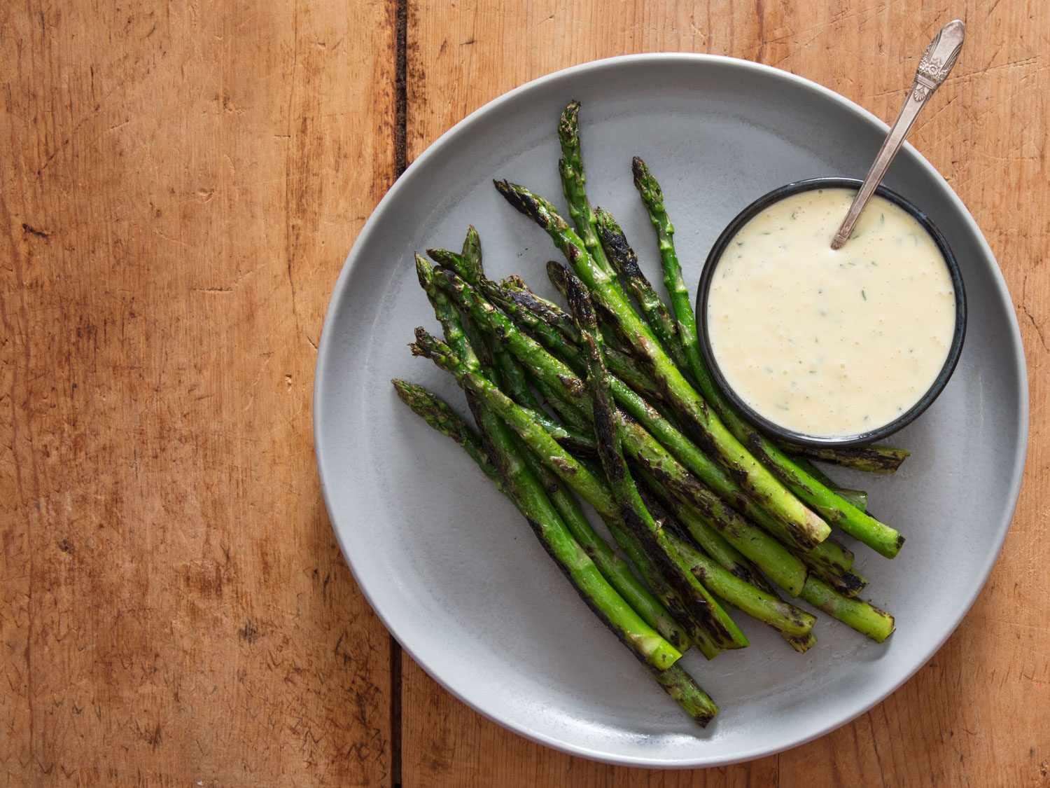 Overhead shot of charred asparagus with a bowl of miso béarnaise.