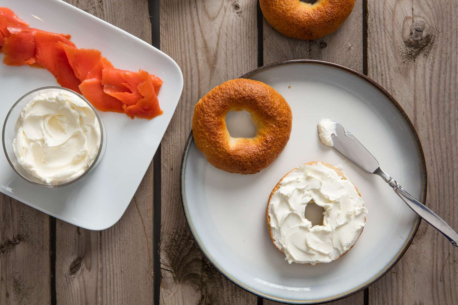 A split bagel on a white plate topped with cream cheese. A platter of cream cheese and lox on the side.