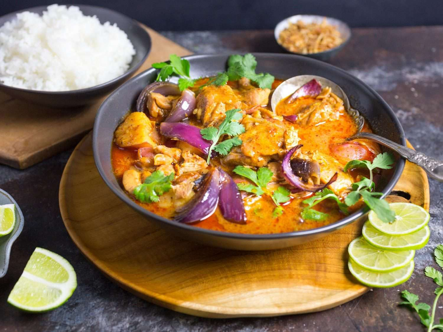 Photo of finished massaman curry in serving bowl surrounded by garnishes, with bowl of rice in background.