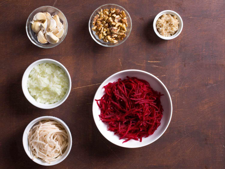 Overhead shot of ingredients for beet-horseradish latkes: shredded beet, shredded potato, chopped onion, garlic cloves, walnuts, and horseradish