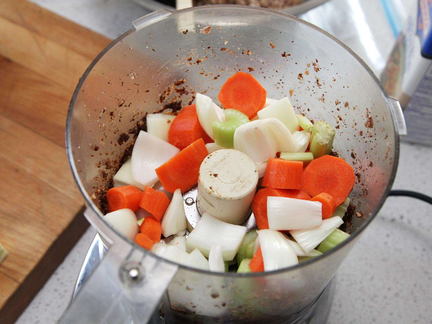 Onion, celery, and carrots in food processor bowl