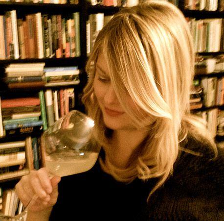 sommelier tasting wine in front of bookshelves