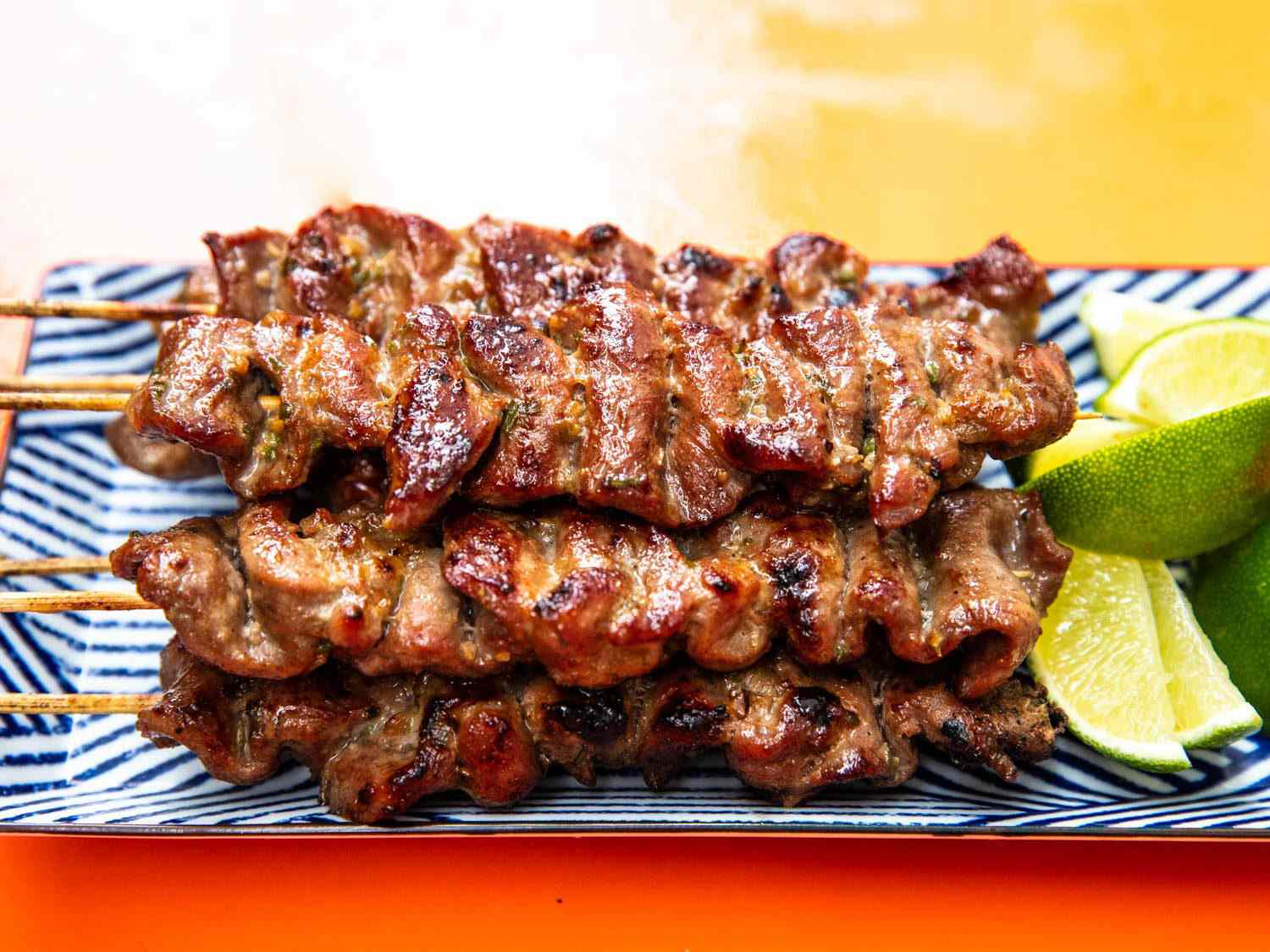 Closeup side view of a platter of THai-style grilled pork skewers with lime wedges