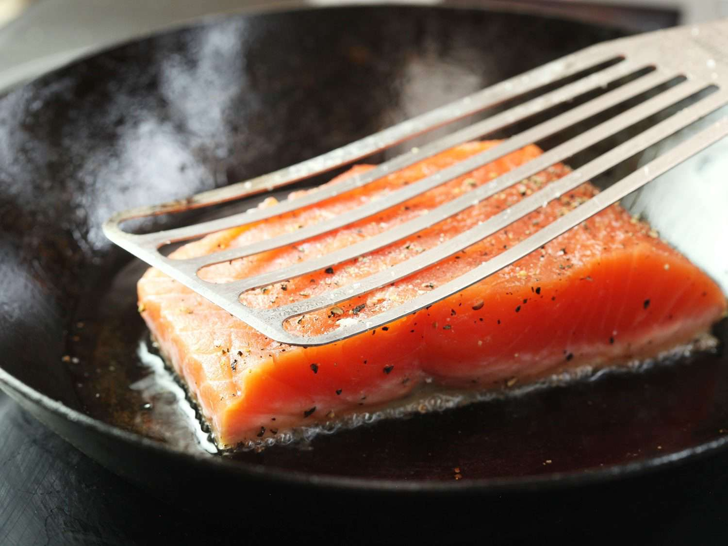 Close-up of a flexible slotted spatula pressing down on a salmon fillet in a skillet