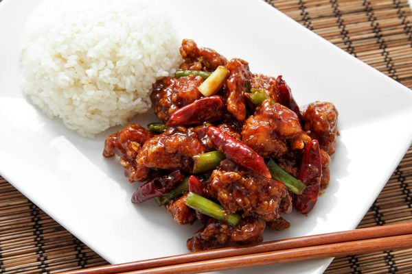 Homemade General Tso's chicken on a white plate next to white rice.