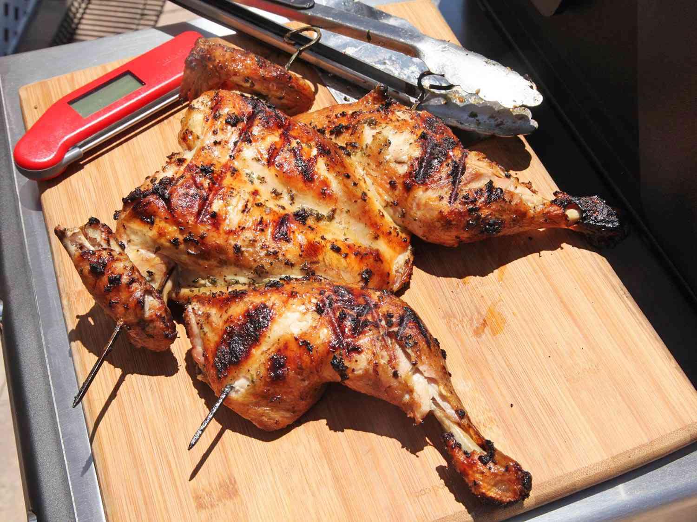 Grilled Greek-style butterflied chicken on a cutting board