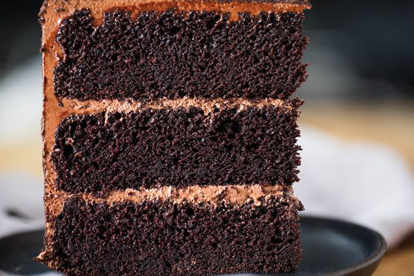 Slice of three-layer devil's food cake on a grey plate.