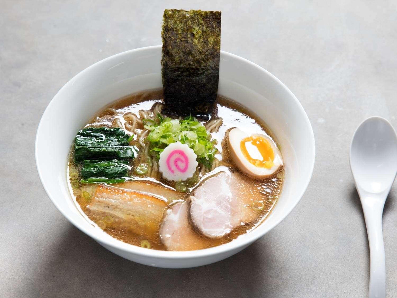 Bowl of shoyu ramen garnished with seaweed, sliced scallion, fish cake, soft-boiled egg, and pork