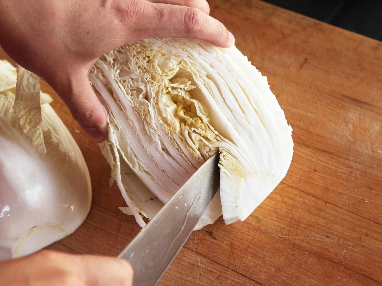 Cutting out the core of a head of Napa cabbage with a chef's knife.