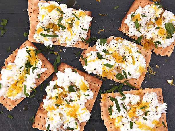 Several pieces of matzo topped with cottage cheese, parsley leaves, and lemon zest