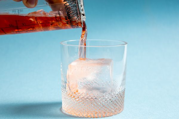 a cocktail being poured over a large ice cube in a rocks glass