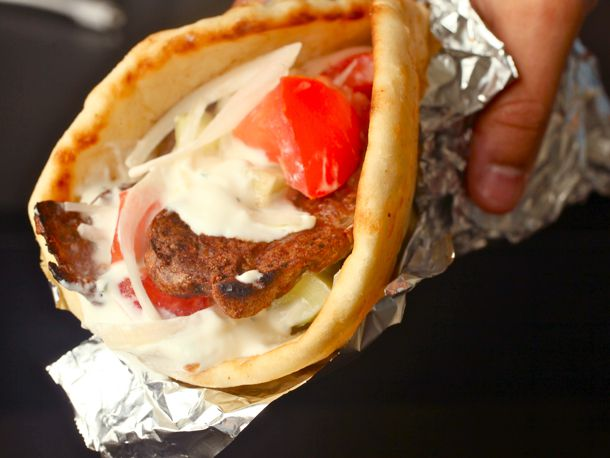 Close up photo of gyro sandwich wrapped in aluminum foil.