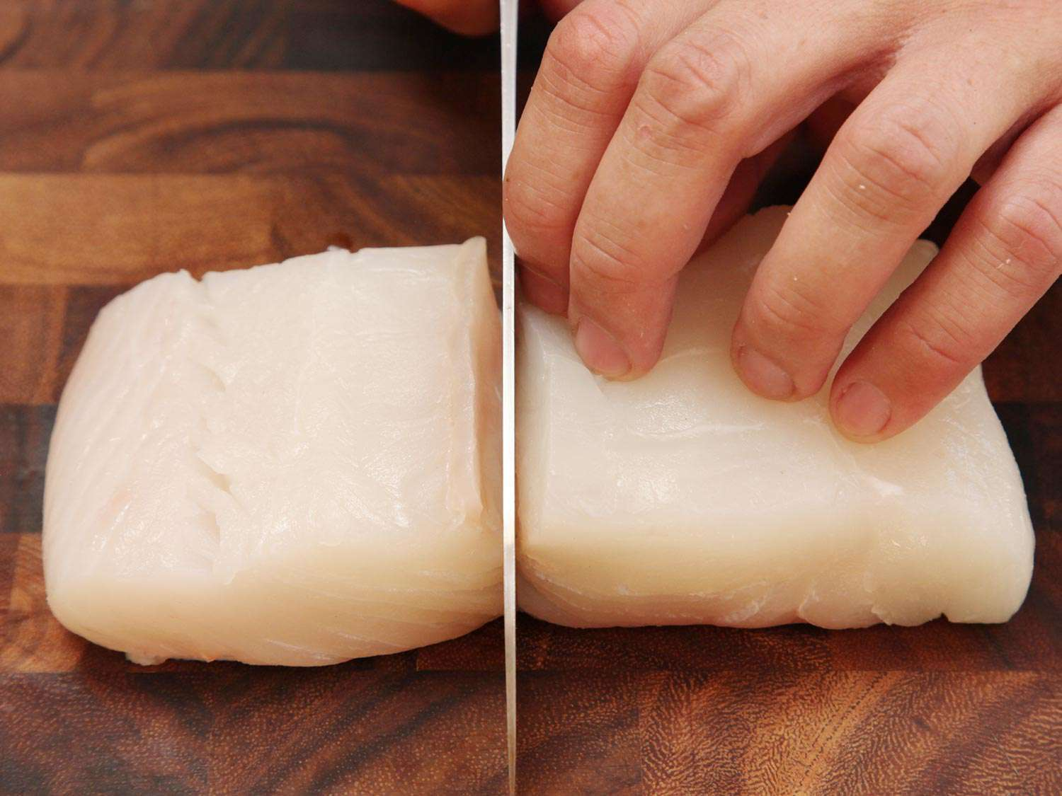 A hand holding an uncooked fish fillet steady while cutting down the middle with a knife into a single portion.