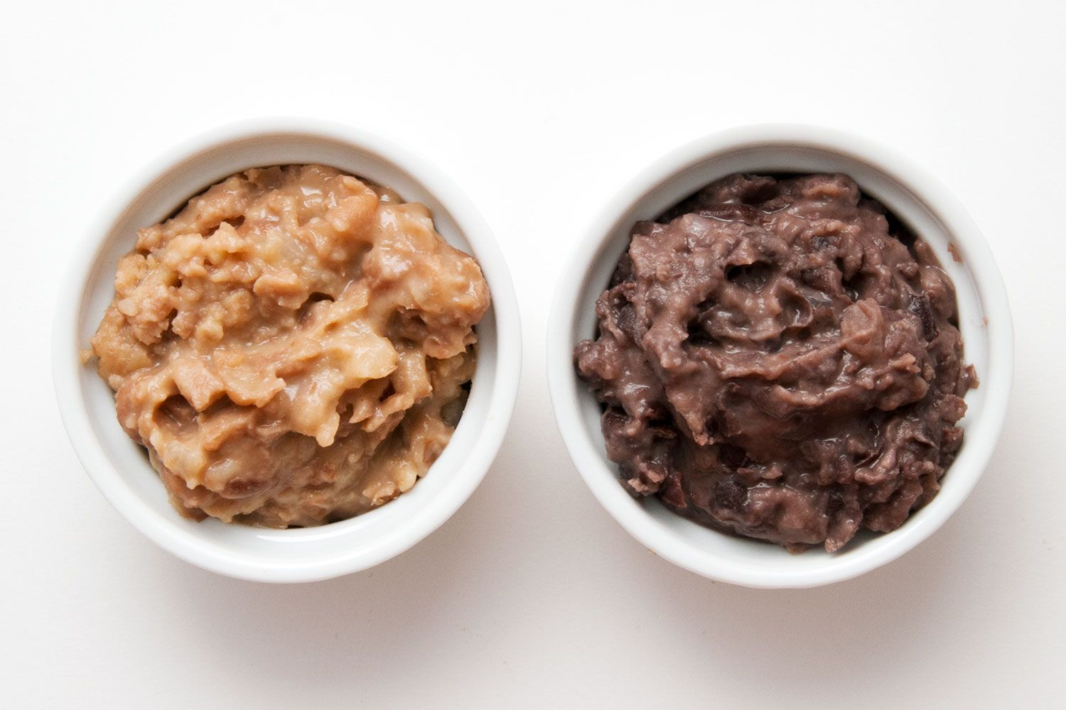 Comparing bowls of refried pinto and black beans