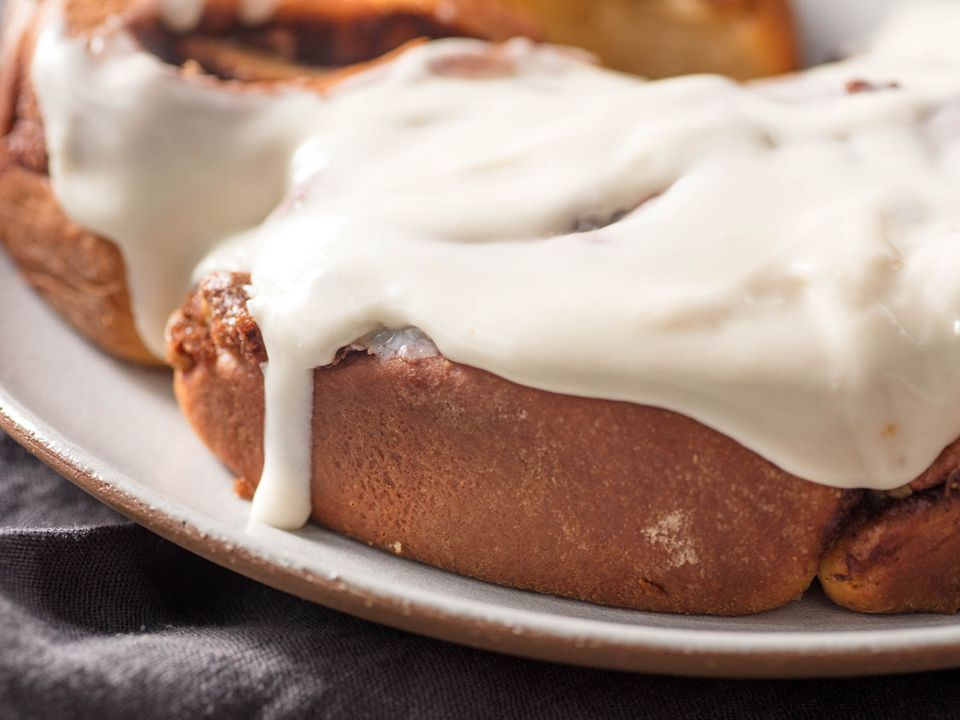 A close-up of overnight cinnamon rolls topped with cream cheese frosting.