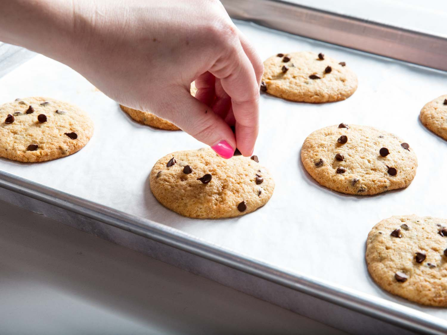 Adding extra chocolate chips to the warm cookies