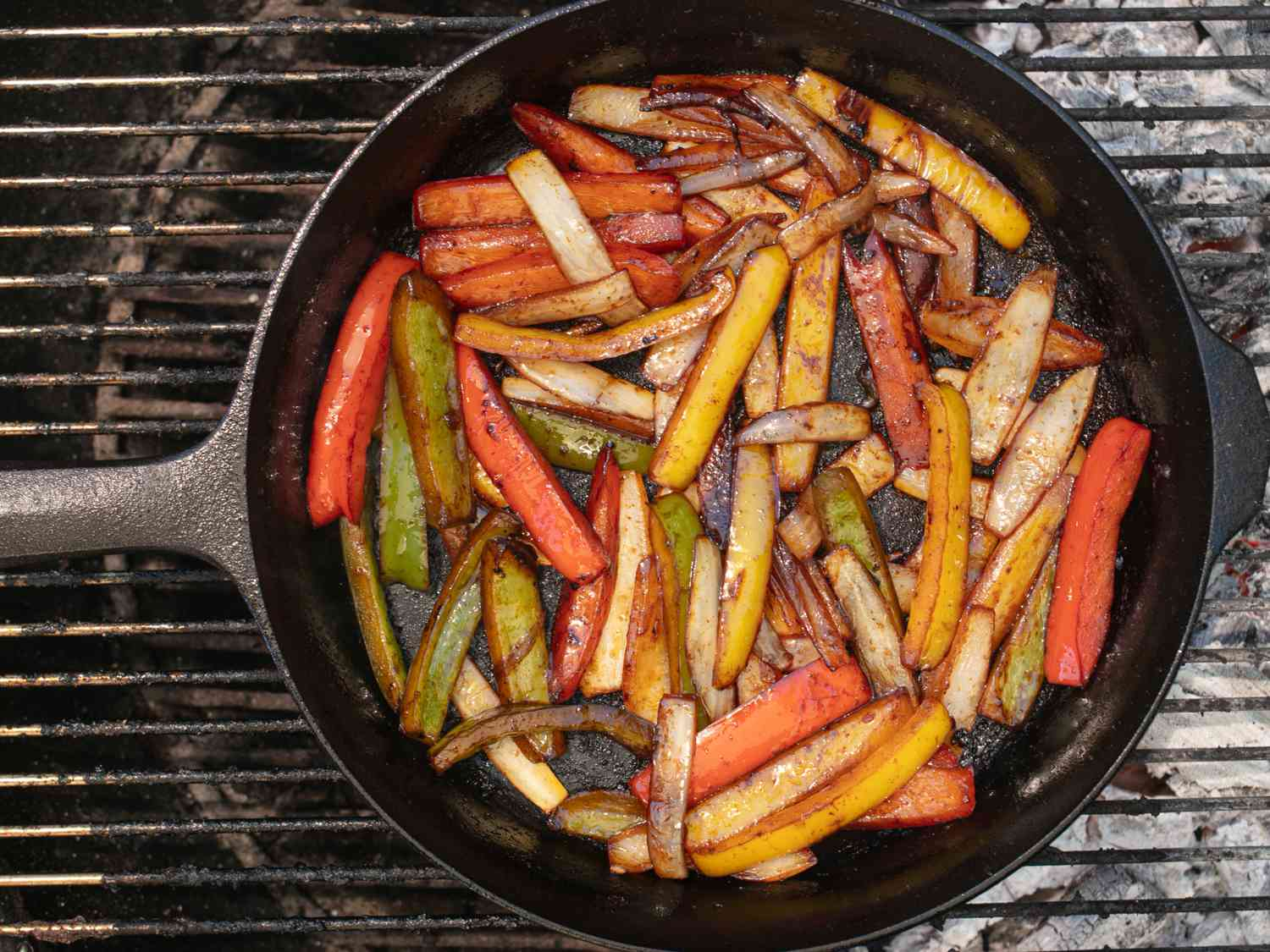 Peppers and onions cooking in a cast iron skillet on a charcoal grill.