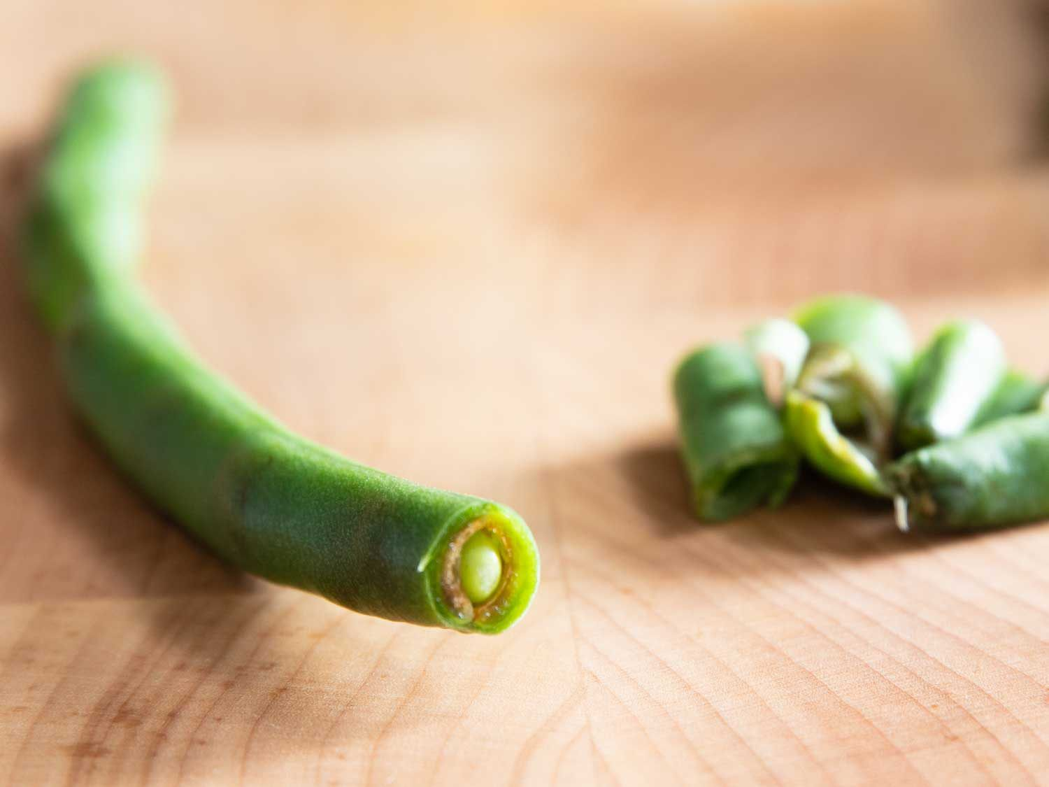 A green bean that has begun to rot on the inside, and is not worth saving.