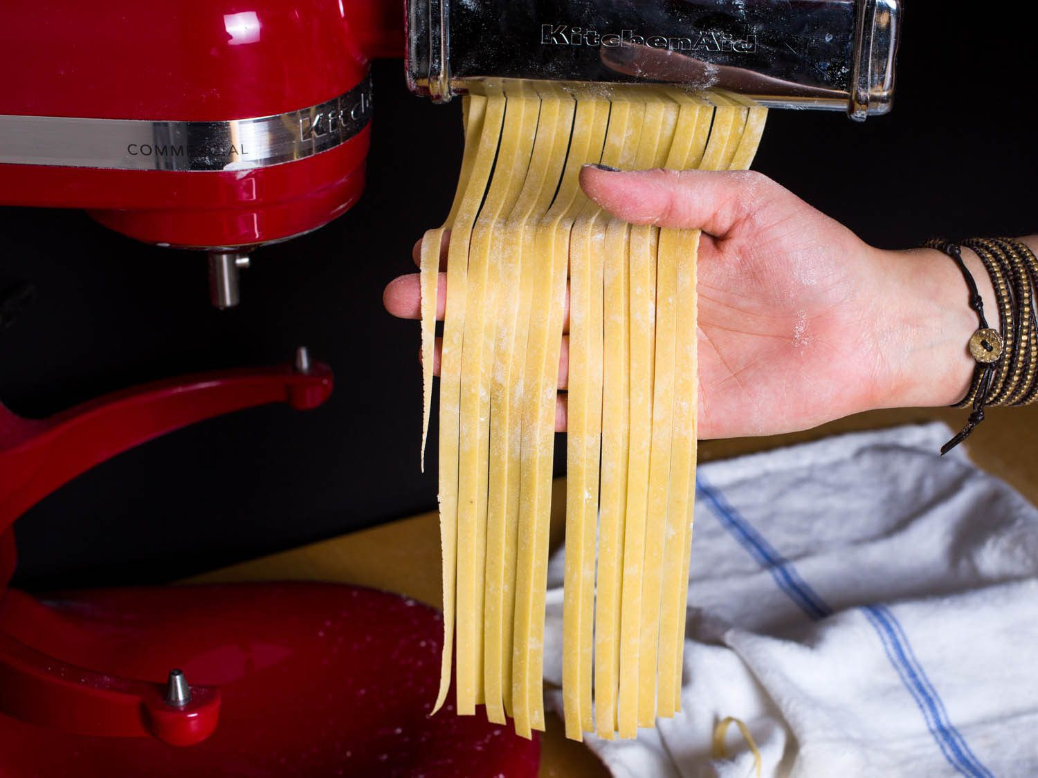 Fresh pasta is fed through a stand mixer attachment