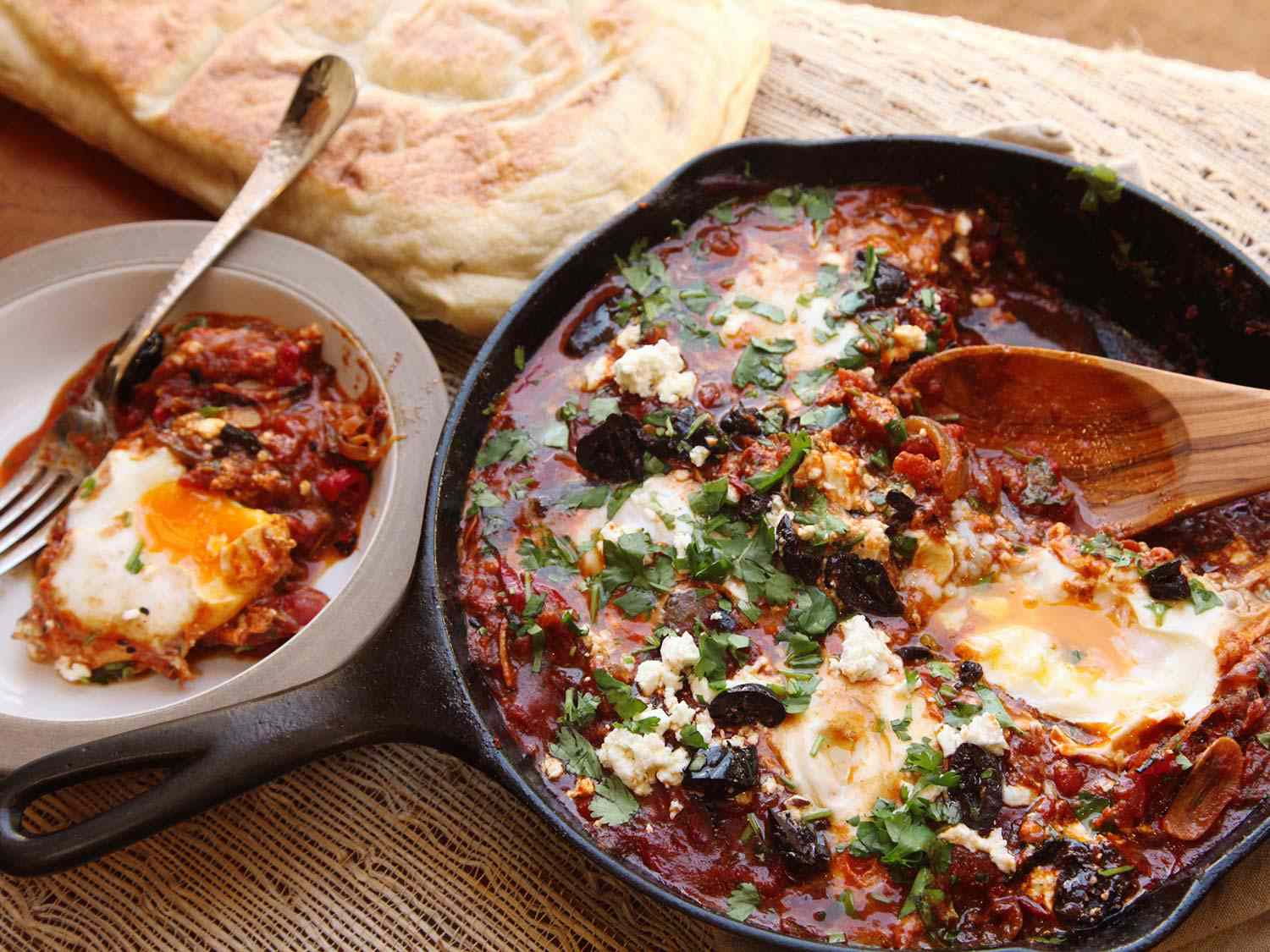 Shakshuka in a cast iron skillet with a serving in a small bowl on the side, with pita bread in the background.