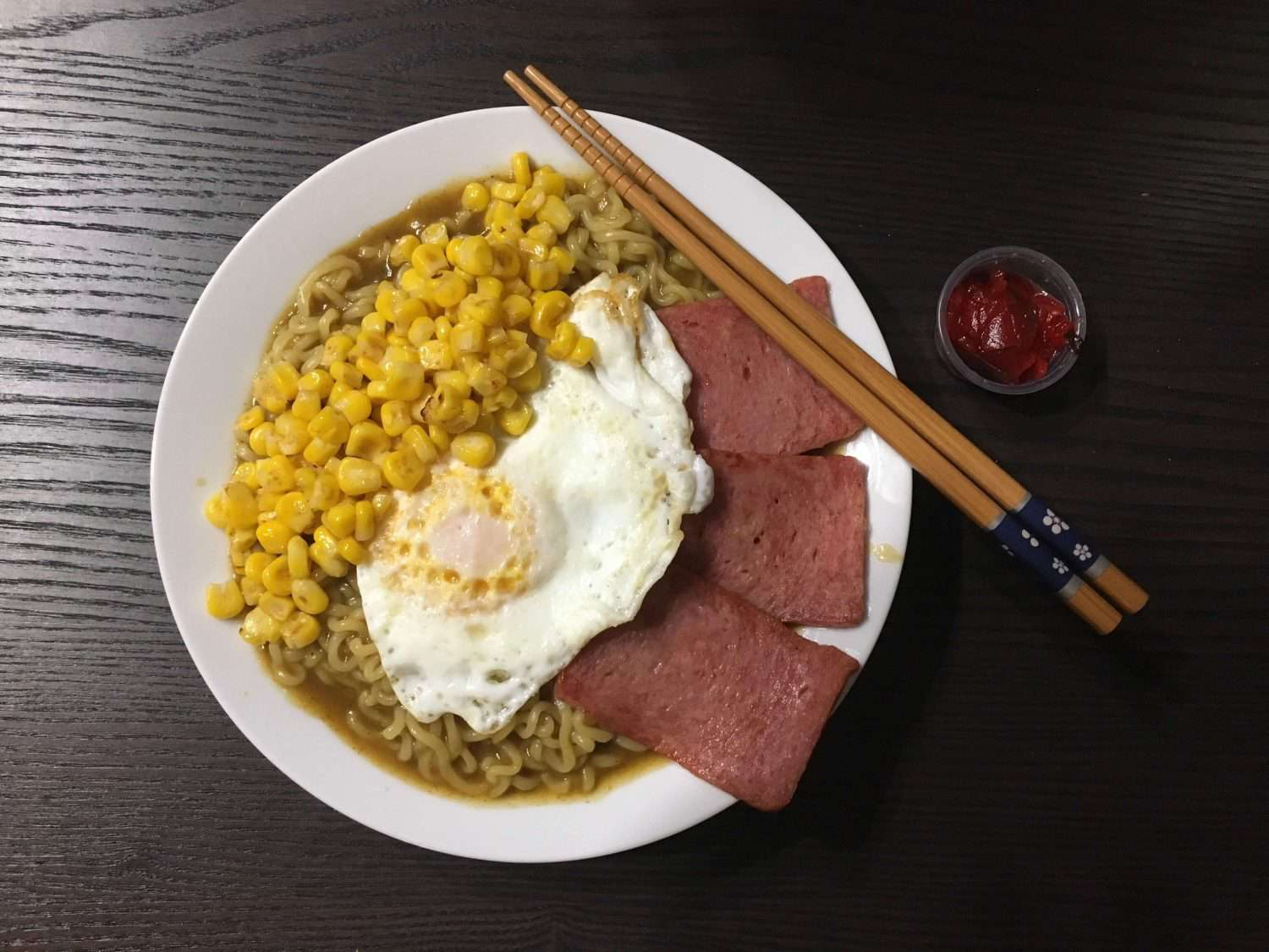 Overhead view of a bowl of curry-men with a fried egg and spam slices