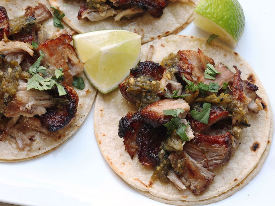 Overhead photograph showing sous vide pork carnitas on corn tortillas topped with salsa verde and cilantro, with lime wedges on the side.