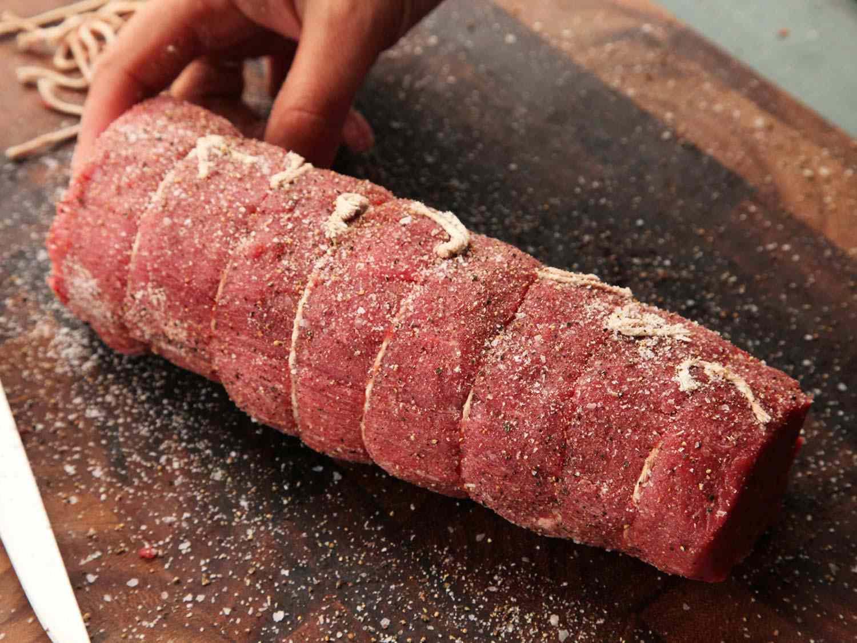 Tied beef tenderloin roast seasoned with salt and pepper